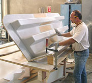 Worker sands fiberglass steps for a Marina Bull forklift.